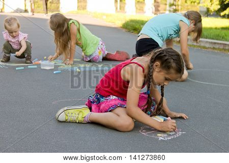 Kids absorbedly draw chalks on the pavement