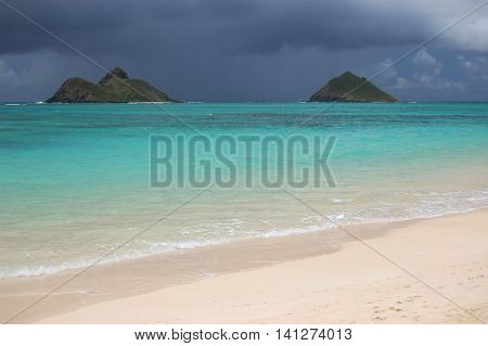 turqoie waters of Lanikai beach with the twin Islands on a background of storm clouds