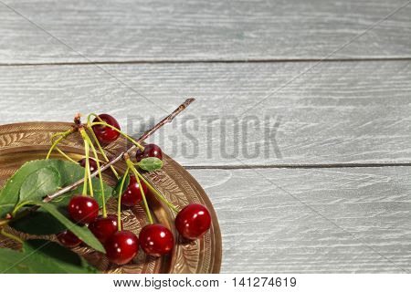 Ripe pulpy cherry on a golden tray