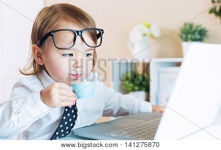 Smart Toddler Girl With Glasses Drinking Coffee While Using A Laptop