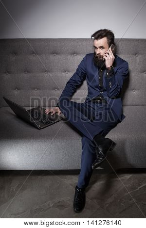 Bearded Man Dressed In Suit And With Laptop And Talk On Phone;