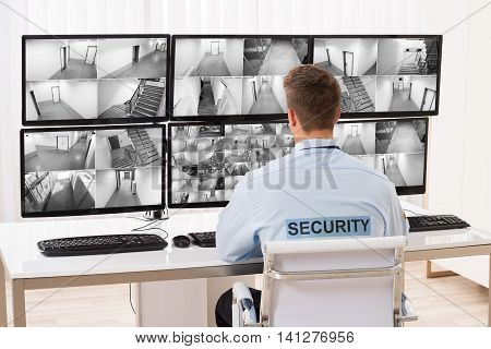 Rear View Of A Young Male Security Guard Monitoring Multiple CCTV Footage