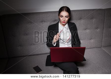 Businesswoman Dressed In Suit And With Laptop And Phone;
