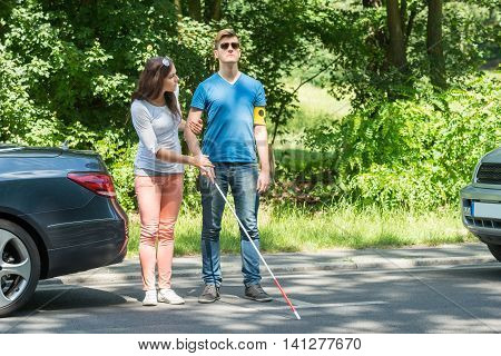 Young Woman Helping Blind Man Wearing Armband On Street