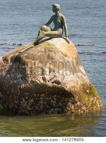 Vancouver Canada - July 24 2016: The bronze statue by Elek Imredy named Girt in a Wetsuit stands on a rock off Stanly Island. She looks at the harbor entrance.