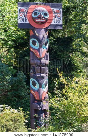 Vancouver Canada - July 24 2016: One of nine totem poles at Hallelujah point in Stanley Park. This one shows a collection of masks in maroon and purple. Green trees as background.