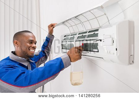 Smiling Male Technician Cleaning Air Conditioner At Home poster