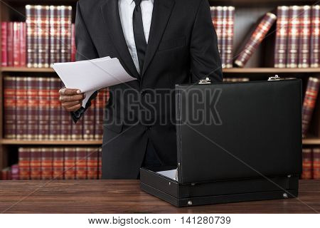 Close-up Of Male Lawyer Removing Papers From Briefcase In Office