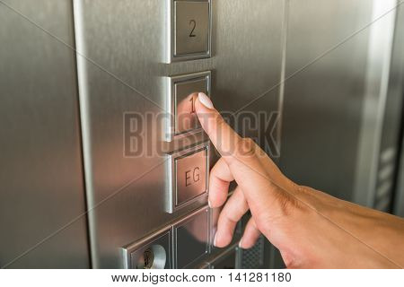 Close-up Of Female's Hand Pressing First Floor Button In Elevator