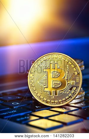 Photo Golden Bitcoins (new virtual money )close-up on a blue background with a computer keyboard.