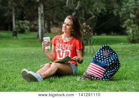 Happy femail tourist is relaxin in park on a grass. Backpack mail and coffee