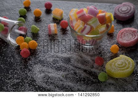 Colorful candies jelly and marmalade and jellybeans around a central copy space on slate on background. Top view with copy space.