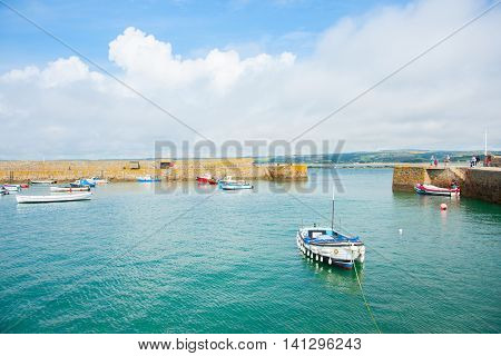 Saint Michael's Mount, England - July 26, 2013: Small boats moored in scenic popuar tourist destination protected walled harbor at St Michael's Mount Cornwall UK
