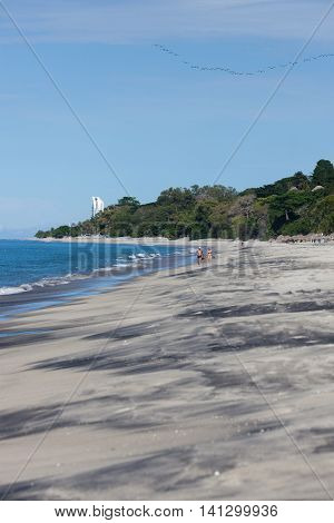 A tropical beach scene with blue waves marbled black and tan sand and people walking in Panama.