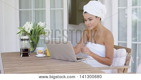 Beautiful woman in bath towel using laptop