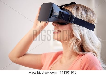 technology, virtual reality, cyberspace, entertainment and people concept - happy young woman with virtual reality headset or 3d glasses at home