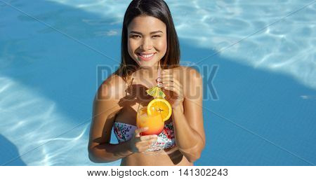 Happy vivacious woman with a tropical cocktail