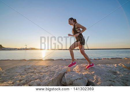 Young Sporty Girl Running Alone At Beautiful Sunset On The Beach