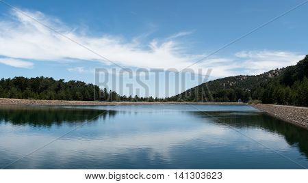 Water reservoir dam with forerst tree reflections at Troodos mountains in Cyprus.