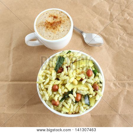 Spicy puffed rice, a popular and traditional Indian snack, in a bowl, and coffee, on a wrinkled brown paper background.