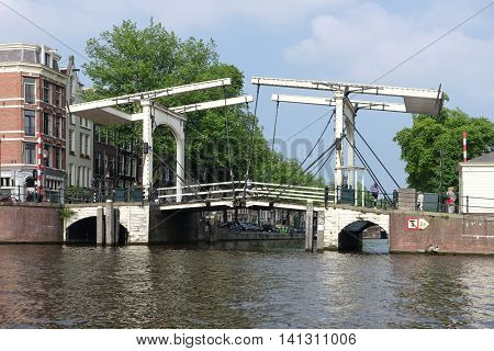 Amsterdam, Netherlands - May 26, 2016: Old white wooden drawbridge where Amstel river meets Nieuwe Herengracht canal Amsterdam Netherlands (next to Hermitage museum). The central section of the bridge is a bascule bridge made of white-painted wood.