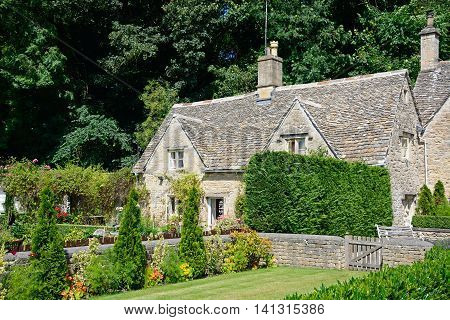 BIBURY, UNITED KINGDOM - JULY 20, 2016 - Pretty Cotswold cottage and garden during the Summertime Bibury Cotswolds Gloucestershire England UK Western Europe, July 20, 2016.