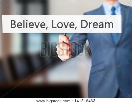 Believe, Love, Dream - Businessman Hand Holding Sign