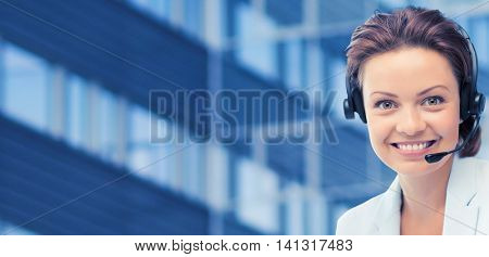 business, people, technology and communication concept - happy female helpline operator in headset over city office building background