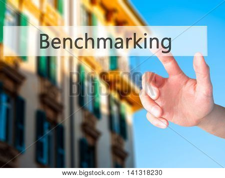 Benchmarking - Hand Pressing A Button On Blurred Background Concept On Visual Screen.
