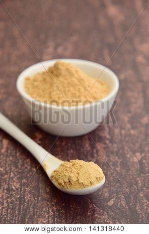 Maca powder on rustic background. Super food