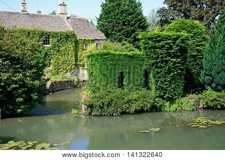Cotswold stone cottage alongside the River Windrush with a weir in the foreground Burford Oxfordshire England UK Western Europe.