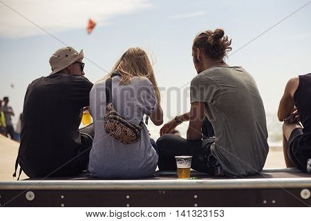 Young skateboarders sit on skatepark in the halfpipe on beach. Urban wallpaper