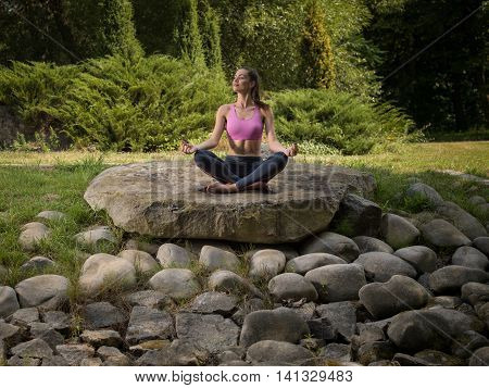 Girl meditates in the lotus position. Among the stones.
