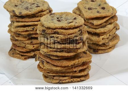 Homemade chewy cookies with chocolate chips on baking paper and white background