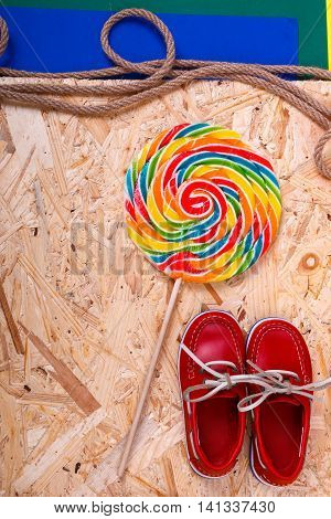 Small red boat shoes near big multi-colored lollipop and rope on wooden desk with colored background. Top view Frame. copy spase.
