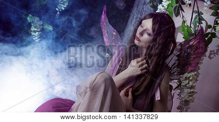 Young beautiful woman in the image of fairies, dark forest