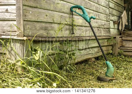 electric grass trimmer stands in the garden near the house simply supported on the wall