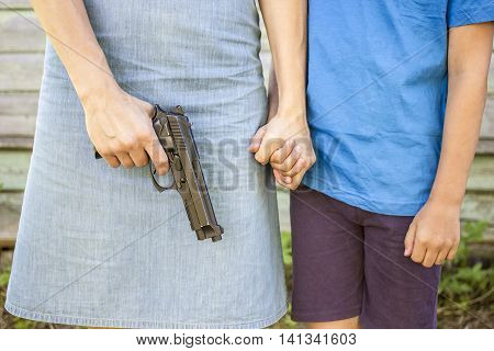 Woman holds the gun nearby there is a the boy whom she strongly holding his hand outdoors