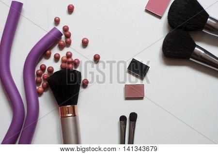 Makeup brushes cosmetics eyeshadow, blush brushes, mirror, eyeshadow, scrub, hair curlers on a white background