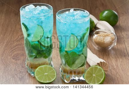 Blue mojito cocktail refreshing summer drink with lime mint and ice on rustic wooden table