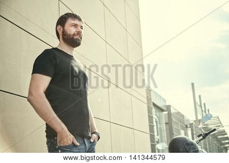 Biker Men With Beard In Black Shirt Standing Near Wall
