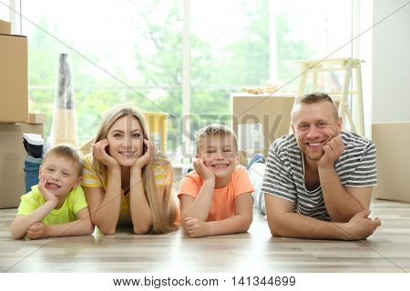 Happy family with cardboard boxes lying on wooden floor