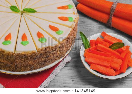 Carrot cake pie sprinkled with nuts decorated with cream-colored carrots on stand for cakes fresh whole carrots sliced sticks carrots on light white background wooden