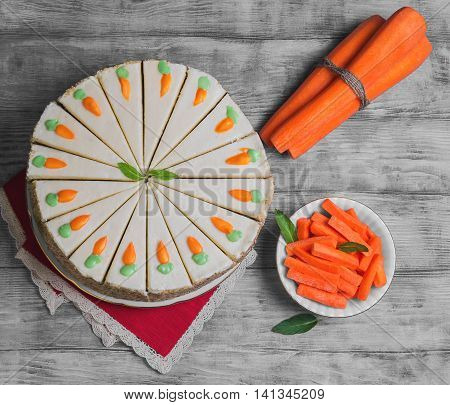 Carrot cake sprinkled with nuts decorated with cream-colored carrots on stand for cakes fresh whole carrots sliced sticks carrots on light white background wooden top view