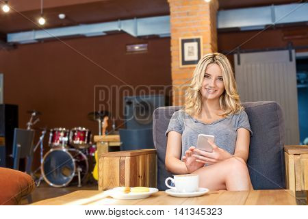 Young Smiling Girl Holding Her Phone And Looking At Camera