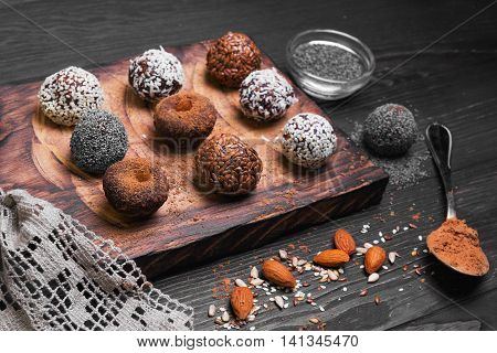 Sweets handmade chocolates sweet-stuff candies sprinkled poppy coconut linseed sesame cocoa almonds oerhi on cutting board with lace on light wooden background in rustic style