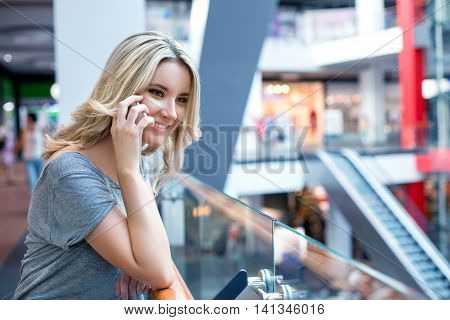 Young Charming Girl Speaking On Mobile Phone In Shopping Center