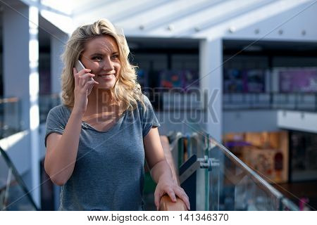 Young Smiling Girl Speaking On Mobile Phone In Shopping Center