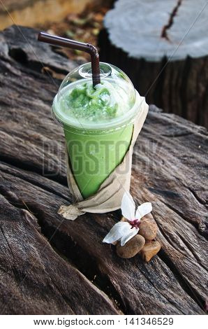 green tea frappe in takeaway cup with nature background