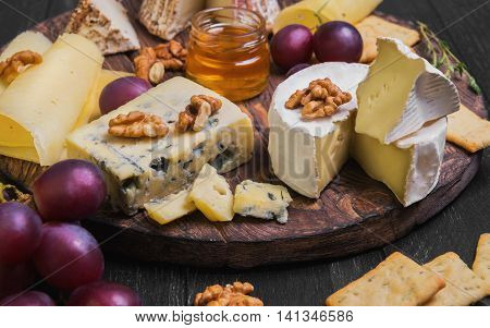 Assorted cheeses on round wooden board plate. Camembert cheese blue cheese goat cheese in the grated bark of oak hard cheese slices walnuts grapes crackers bread thyme honey sauce dark black wood background